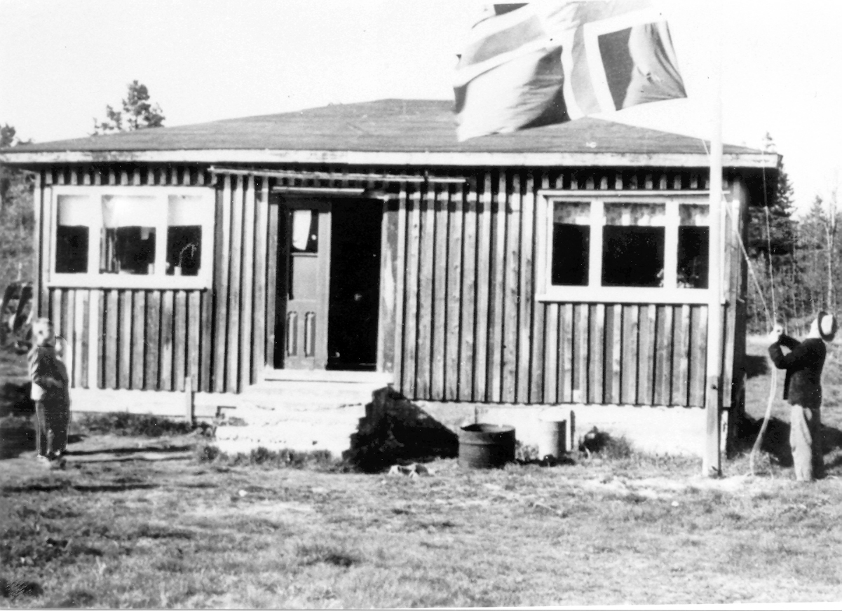 """FLAGGHEIS: Jens Bøya heiser flagget utenfor """"bungalowen"""" ute i Nyhaven. Til venstre står Martin Birkeland og Olav Røstad. Bildet, som er tatt rundt 1960, er utlånt av Birkenes Kameraklubb."""