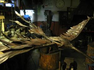 SKINNENDE FJÆR: Det skinner i fjærene på Fugl Phoenix der den står utstilt i smia før den slipper ut og får luft under vingene for aller første gang. Fuglen skal monteres på en jernstang som fundamenteres i bakken.