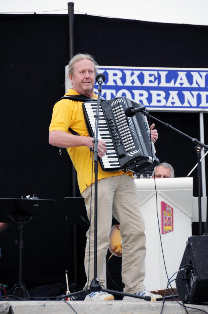 GJESTEDIRIGENT: Om det blir trekkspillmusikk er vel heller tvilsomt, men passelige doser skjemt og moro, blir det garantert, sammen med feiende marsjtoner, når Geir Knutson gjør en gjesteopptreden som dirigent for Birkenes Hornmusikk torsdag kveld. Her er han i sving med Birkeland Storband på Tobias Jorde sommeren 2011.