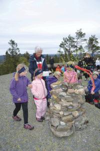 SKRIN I VARDEN: Som eldste kvinne i forsamlingen fikk Magnhild Knutson (88) æren av å plassere glassfiberskrinet inne i den nybyggede varden. Hun fikk assistanse av de aller yngste. Steinene i varden var fraktet opp av deltakerne, som la på hver sin stein etter hvert som de ankom det flotte platået oppe på Heimdalsknuten.