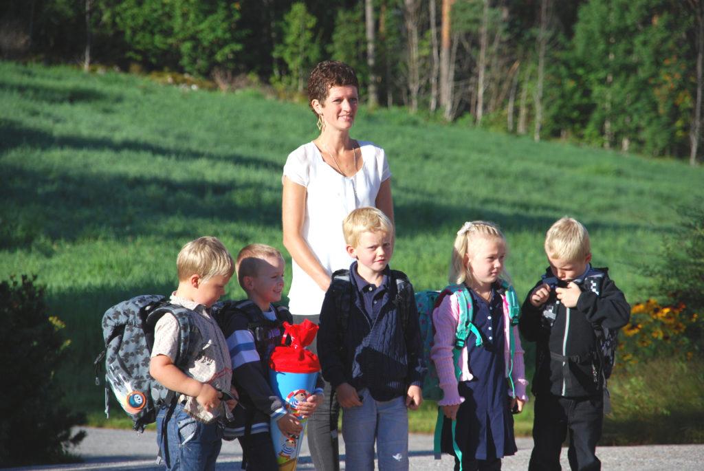 HEREFOSS: Kontaktlærer Arnhild Brakestad har samlet de fem førsteklassingene som er klare til å ta fatt på sin aller første skoledag. (Foto: Elsie Holm)