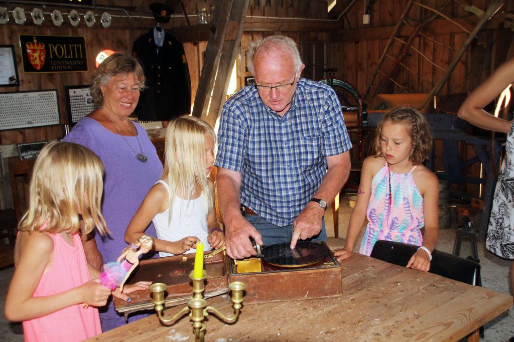 OMVISNING: Jentene fikk en omvisning på gården, og Helge fortalte om mange av de gamle tingene som er samlet der i årenes løp, som denne grammofonen av edel årgang. Artikkelforfatteren i bakgrunnen.