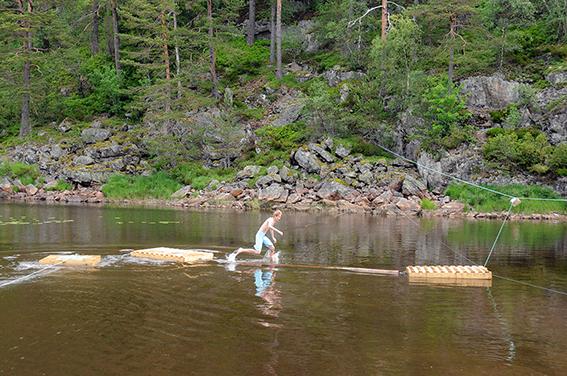 VANNHINDERLØYPE: Tobias fra 1. Vennesla Gaupe gir seg i kast med å «gå planken» etter å ha trukket seg ut med trekkflåten til venstre. Vel over på den andre flåten var det å trekke seg inn til land via vaieren til høyre og slå i målsteinen.