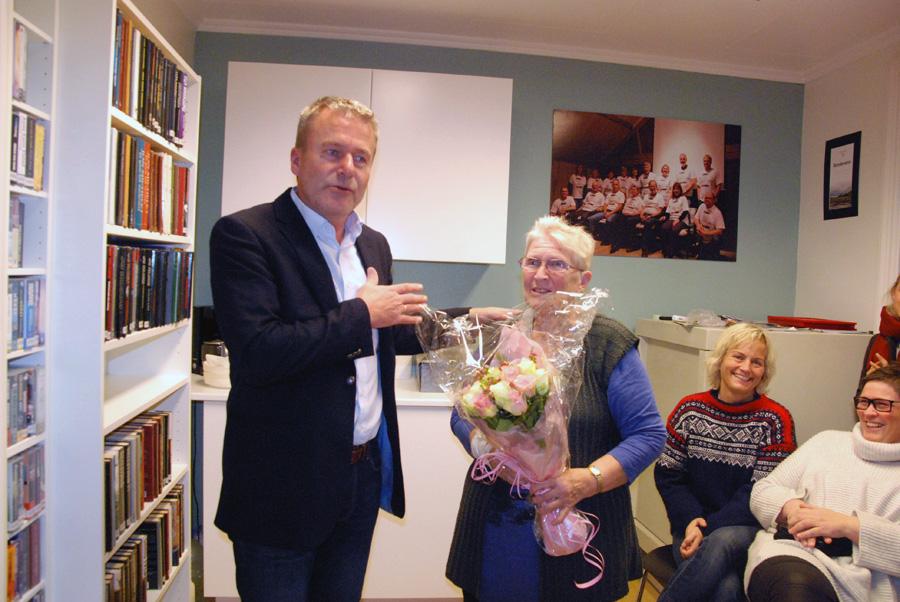 OVERREKKELSE: Sjefen i Birkens Sparebank Harald Flaa overekker Signe Fidje blomster for hennes engasjement i bokkafeen.